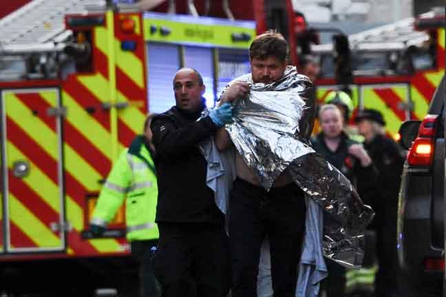 Anggota polis membantu mangsa yang cedera selepas seorang lelaki bersenjatakan pisau menikam beberapa orang di London Bridge di London, Britain kelmarin. — Gambar Daniel Sorabji/AFP