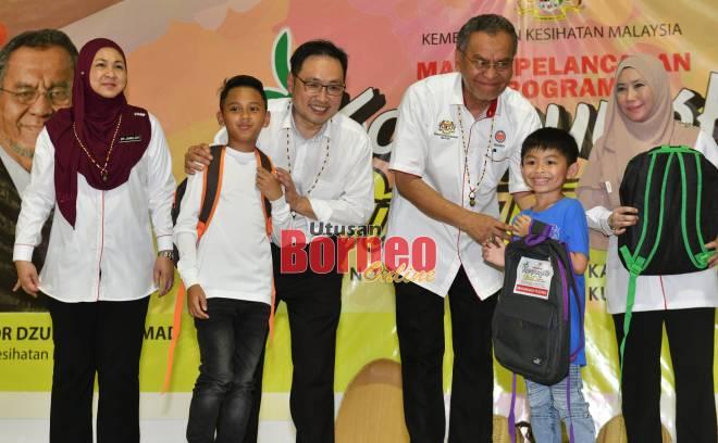 Dr Dzulkefly ditemani Chong menyampaikan beg sekolah kepada murid sempena program Kampungku Sihat Peringkat Parlimen Stampin di Kampung Tematu.