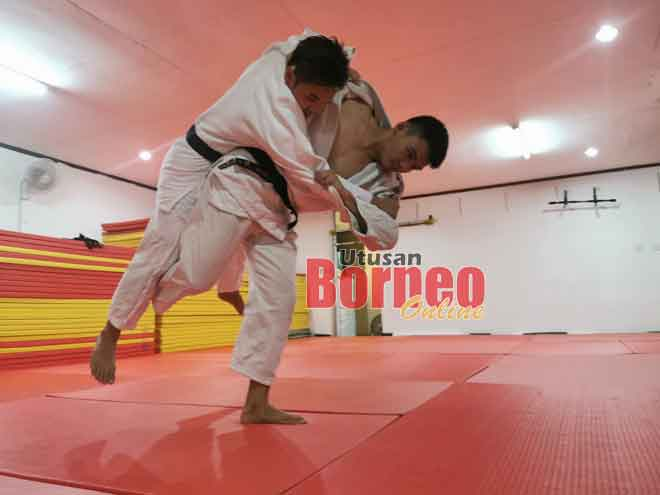 Brenton (kanan) mengadakan 'sparring' dengan atlet judo Sarawak Soh Yew Ing semasa latihan.