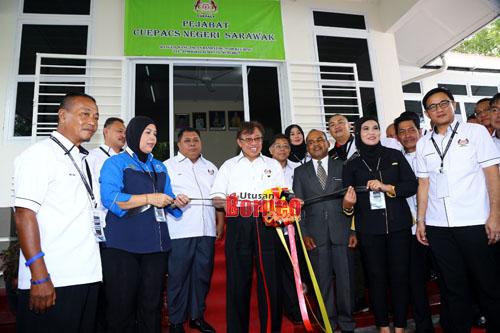 Abang Johari memotong riben sebagai simbolik perasmian Pejabat CUEPACS Sarawak di Jalan  Bampfyle Kuching. Turut kelihatan (belakang, dari dua kiri) Ahmad dan Azih. - Gambar oleh Muhammad Rais Sanusi