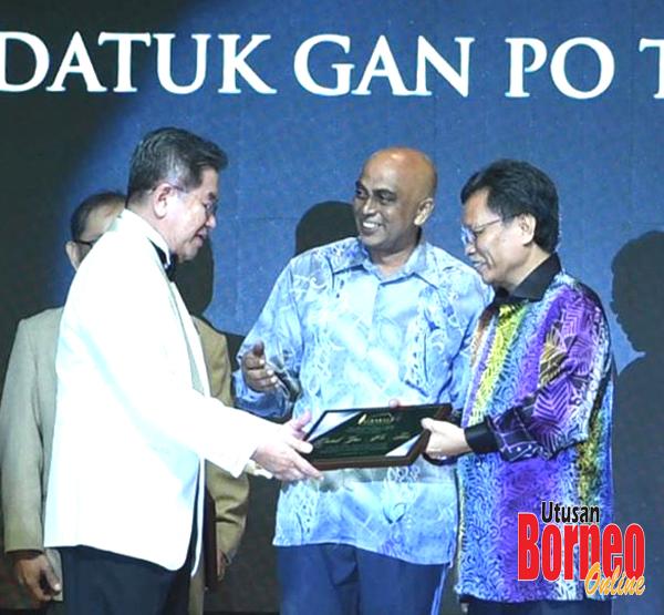 Gan (kiri) menerima anugerah daripada Shafie pada majlis itu.