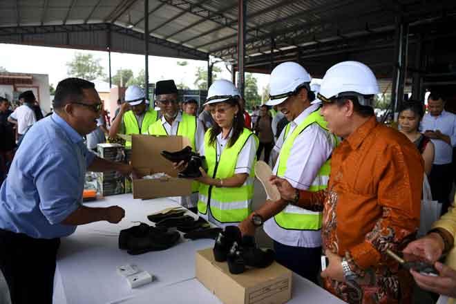 Teresa Kok (tengah) melihat kasut yang dihasilkan daripada pokok kenaf ketika merasmikan Pusat Industri Kenaf di Kampung Tebu Hitam semalam. — Gambar Bernama