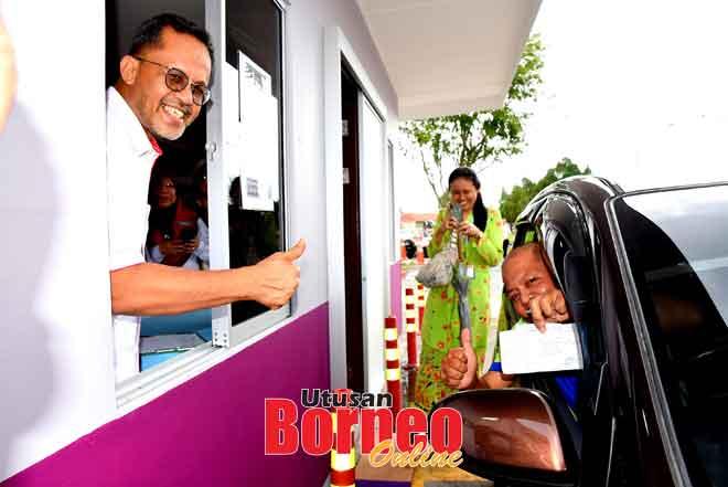 Dr Ramli (kiba) lebuh ti nyuaka ubat ngagai Roslan ti nyadi orang keterubah ngena servis 'Farmasi Pandu Lalu' ba Sepital Sibu.