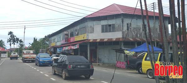 Pemandangan kedai di pekan lama Bongawan yang dibina daripada kayu masih beroperasi, sementara di sebelahnya telah banyak dibina bangunan komersil konkrit.
