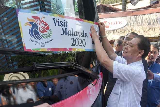 Mohamaddin melekatkan pelekat kenderaan MATTA yang dilancarkan sempena Tahun Melawat Malaysia 2020 (VM2020) pada sebuah bas di Pusat Pelancongan Malaysia (MaTiC) semalam. — Gambar Bernama