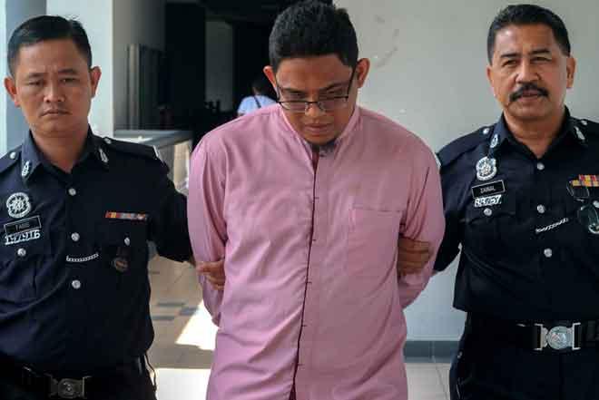 Muhammad Zaki (tengah) mengaku tidak bersalah di Mahkamah Majistret Melaka semalam atas pertuduhan mencederakan isterinya dengan cara menumbuk muka, mencekik dan memijak badan mangsa pada Mei tahun lepas. — Gambar Bernama