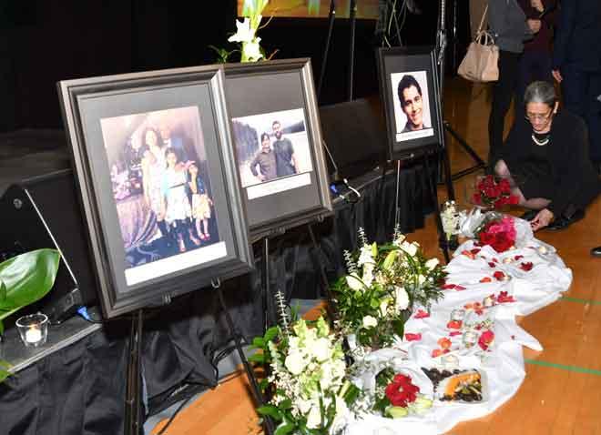 Orang yang menghadiri pengebumian meletakkan bunga berdekatan gambar mangsa-mangsa di hadapan pentas sebelum upacara berdoa untuk 57 mangsa rakyat Kanada dalam nahas pesawat Ukraine di Iran. — Gambar AFP