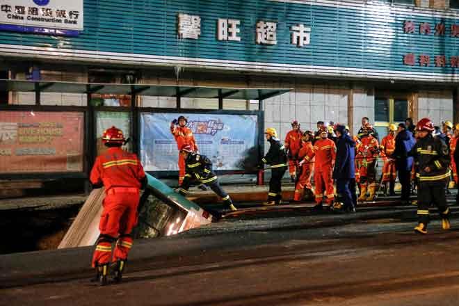 Gambar yang dirakam kelmarin menunjukkan anggota penyelamat cuba mengangkat keluar bas yang tenggelam di dalam lubang benam di sebatang jalan di Xining, wilayah barat laut Qinghai. — Gambar AFP