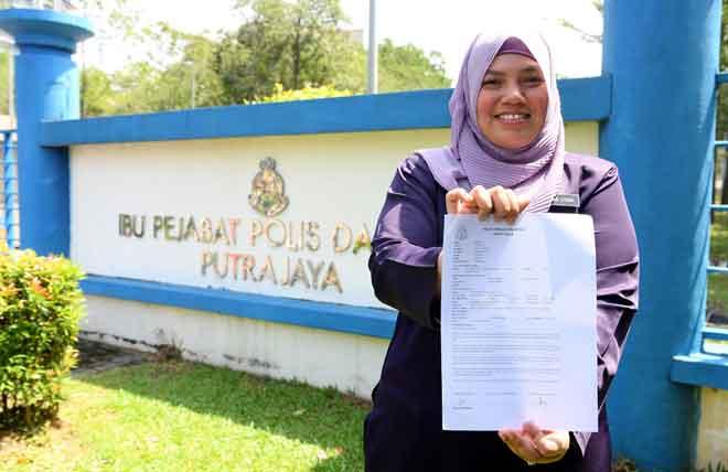 Sasha menunjukkan salinan laporan polis kepada pengamal media selepas membuat laporan polis terhadap beberapa individu termasuk peguam yang didakwa menjadi dalang dalam komplot jenayah untuk menjatuhkan reputasi dan imej suruhanjaya itu dan Latheefa di Ibu Pejabat Polis Daerah Putrajaya, semalam. — Gambar Bernama