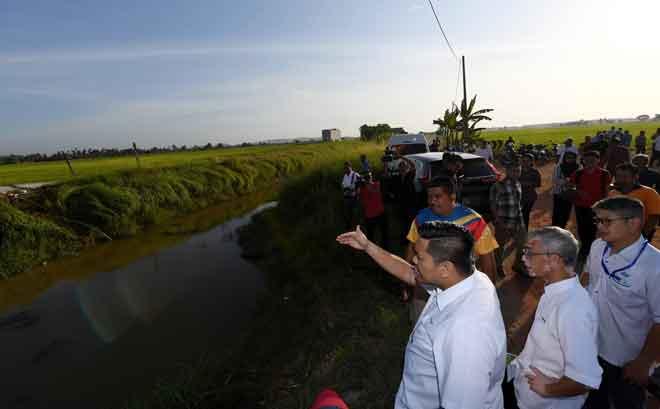 Dr Afif B (tiga, kanan) meninjau kawasan tali air yang kekurangan air untuk kegunaan sawah padi susulan musim kemarau sehingga menyebabkan produktiviti padi dan pendapatan pesawah menurun, di Kampung Paya Keladi semalam. — Gambar Bernama