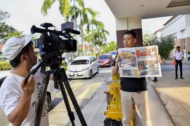 Krew Asahi TV dari Jepun mengulas berita kemalangan Kento Momota yang disiarkan surat khabar tempatan semasa membuat liputan perkembangan pemain badminton nombor satu duniaitu di Hospital Putrajaya semalam. — Gambar Bernama