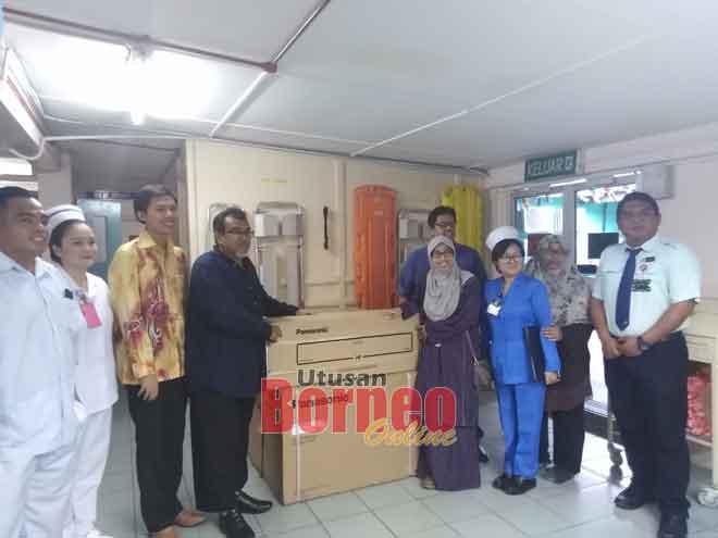 Hasbi (empat kiri) menyerahkan alat pendingin hawa kepada Dr Nur Hazwani pada majlis ringkas  di Limbang, semalam.