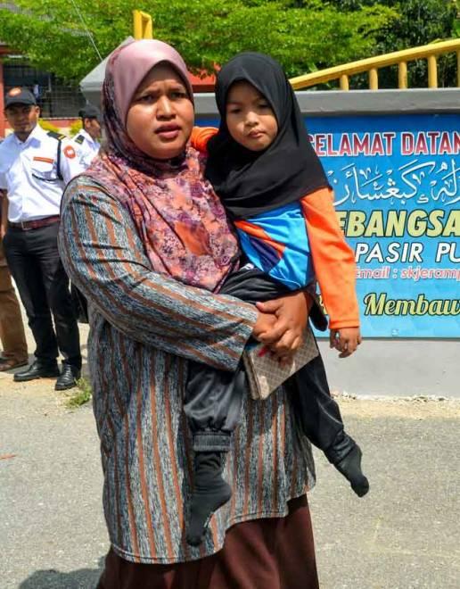 Nur Amni Zahra  didukung ibunya Siti Noraini untuk pulang ke rumah di Sekolah Kebangsaan Jeram di Pasir Puteh. Siti merayu kepada mana-mana pihak bagi memberi sumbangan kerusi roda dan tongkat bagi membantu Nur Amni Zahra bergerak terutama di sekolah berikutan keadaan kedua-dua kaki anaknya yang berbeza panjangnya. — Gambar Bernama