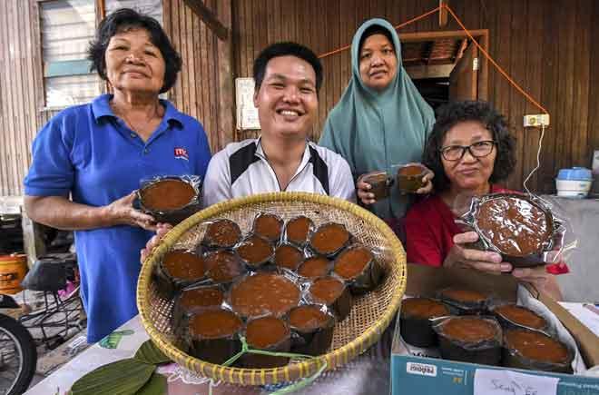 Tan (dua kiri) bersama ibunya Kam Guat Thee (kanan), ibu saudaranya Tan Chui Huai, 65, (kiri) dan jiran, Rosliza Hasan, 49, (dua kiri) menunjukkan kuih bakul yang dihasilkan mereka di Kampung Pantai Kemayang, Tawang di Bachok.  — Gambar Bernama