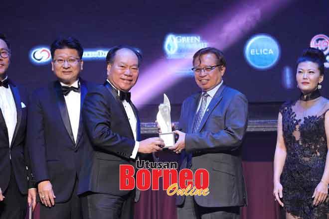 Ketua Menteri Datuk Patinggi Abang Johari Tun Openg (kanan) menyampaikan Anugerah SHEDA untuk Pembangunan Strata kepada Isaac.