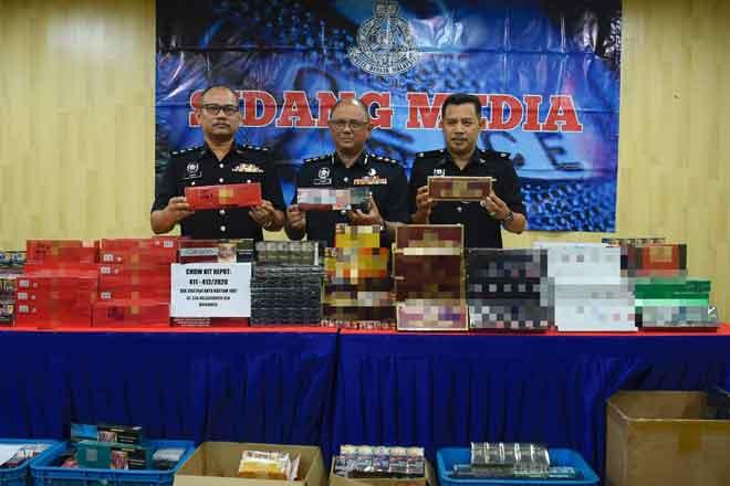 Mohd Fahmi (tengah) menunjukkan rokok seludup yang dirampas semalam selepas sidang media di Ibu Pejabat Daerah Dang Wangi, Kuala Lumpur. — Gambar Bernama