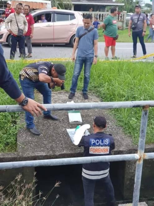 Polis memeriksa mayat bayi yang dijumpai dalam longkang.