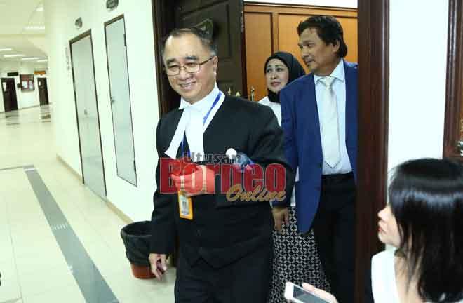 JC Fong keluar dari kamar mahkamah selesai prosiding. Turut kelihatan Hasidah dan Idris.