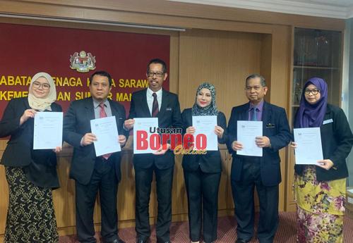 Awang Raduan (tiga kiri) menunjukkan dokumen berkenaan penguakuasaan Perintah Gaji Minimum 2020 bersama kakitangan JTK Sarawak di Kuching hari ini.