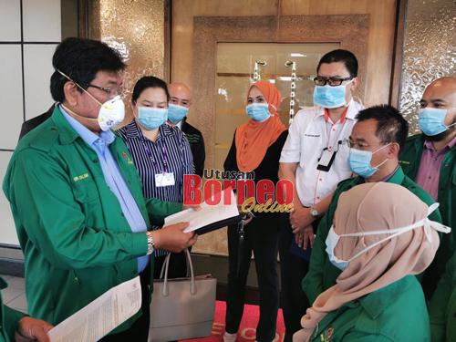 Nor Halim (dua kiri) menunjukkan kenyataan langkah-langkah pengawalan terhadap jangkitan Koronavirus bersama kakitangan JKKP lain dan wakil dari Malaysia Airport Sdn Bhd serta Jabatan Kesihatan Negeri. - Gambar oleh Roystein Emmor