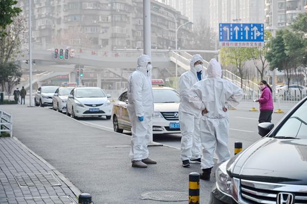 Para petugas memakai pakaian pelindung di satu jalan di Wuhan pada 30 Januari 2020.
