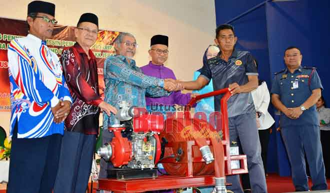 Abdul Kadier (tiga kiri) menyerahkan mesin dan peralatan pemadam api kepada wakil G7 JKKK Kampung Jepak sambil disaksikan Talib (tengah), Temenggung Rosli, Penghulu Drahman (kiri), Dr Zaliha dan Unjar (kanan).