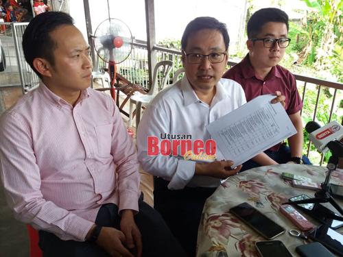Chong (tengah) menunjukkan surat yang dikeluarkan Jabatan Perbendaharaan Negeri bagi memaklumkan mengenai cukai jualan yang dikenakan ke atas tayar.