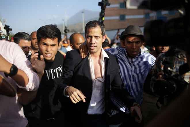 Guaido diapit pengiring keselamatan ke keretanya sejurus tiba di Lapangan Terbang Antarabangsa Simon Bolivia di Maiquetia, negeri Vargas, Venezuela kelmarin. — Gambar AFP