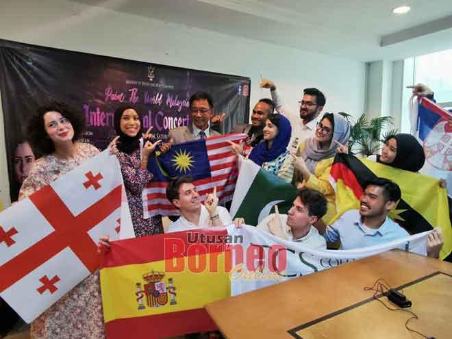 Abdul Karim begambar enggau tim Paint the World Malaysia ti betuaika Aziza (bediri, kiba)sereta disempulang ke bukai pengudah nemuai meri basa, ensanus.-— Gambar Roystein Emmor
