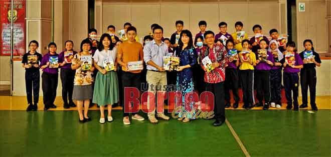 Ling (empat kiri) menyerahkan majalah 'Saintis Muda' kepada Chua di Sibu, semalam.