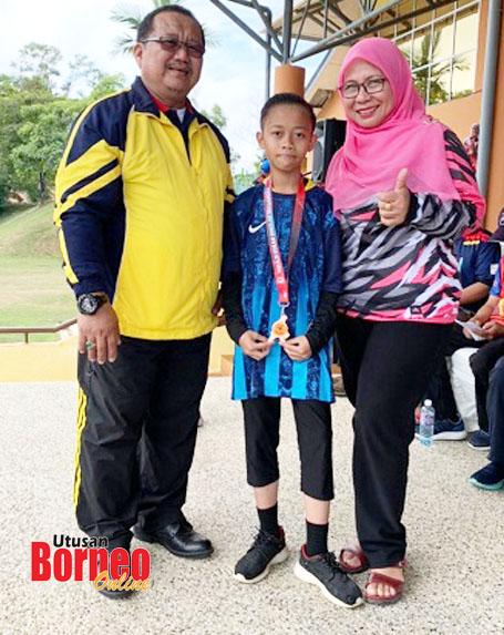 Mohd Afiq menerima pingat tempat ke-4 daripada Guru Besar SK Patau-Patau, Sazali Haji Dinin selaku pengelola Kejohanan Merentas Desa Peringkat MSSWP Labuan 2020 sambil diperhatikan Guru Besar SK Sungai Bedaun, Dg Sarifah.