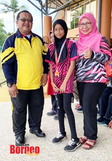 Guru Besar SK Sungai Bedaun, Dg Sarifah memerhatikan Nur Washfasha menerima medal tempat ke-3 daripada Guru Besar SK Patau-Patau, Sazali Haji Dinin selaku pengelola Kejohanan Merentas Desa Peringkat MSSWP Labuan 2020.