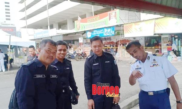 Kapten (M) Zainudin berkata sesuatu kepada pegawai polis terlibat.