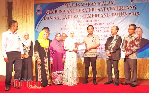 Sarifuddin menyampaikan hadiah khas kepada salah seorang penerima Anugerah Pusat Cemerlang.