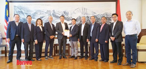 Peter (lima kiri) menyerahkan cek dan surat kepada Liang (enam kanan) sempena dengan kunjungan hormat itu.