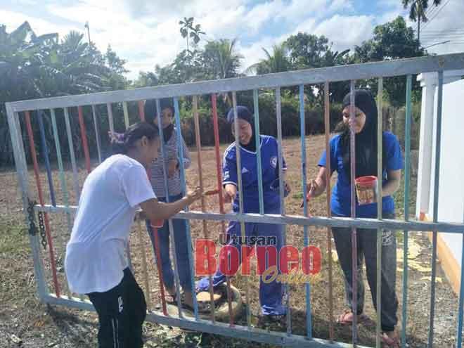 Ahli KRT Rangau sedang mengecat kawasan pagar tabika.