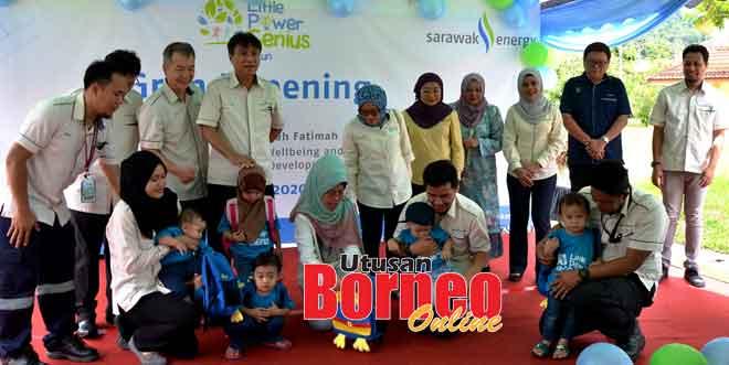 Fatimah (tengah) menyampaikan beg sekolah kepada anak-anak kakitangan SEB sambil disaksi pengurusan kanan SEB.