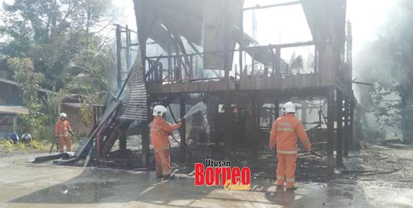 Anggota bomba berusaha memadam kebakaran daripada terus merebak.