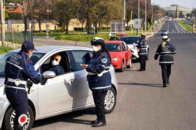 Anggota Polis Tempatan Rom membuat semakan dokumen pengesahan ke atas pengguna jalan raya di Via Pontina, di Rom, kelmarin ketika negara tersebut menguatkuasakan 'lockdown' bagi menghentikan penyebaran  COVID-19. — Gambar  AFP