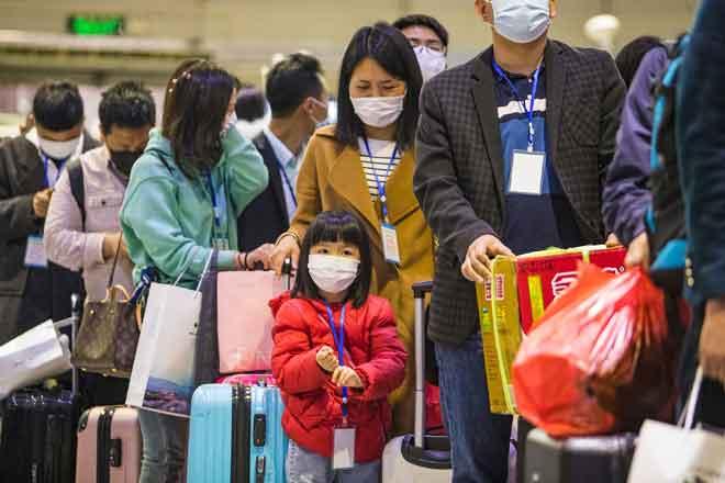 Pekerja asing bersama keluarga mereka berbaris untuk menaiki kereta api khas ke Shenzhen, di Yichang, wilayah tengah Hubei kelmarin. China mengumumkan sekatan perjalanan ditarik balik di wilayah tersebut selepas perintah berkurung selama dua bulan untuk membendung COVID-19. — Gambar AFP