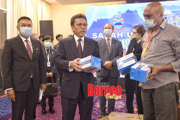 Shafie (tengah) menyampaikan sumbangan topeng muka untuk media yang diwakilkan oleh Presiden Persatuan Wartawan Sabah (SJA) Datuk Muguntan Vanar (kanan) selepas sidang media itu.