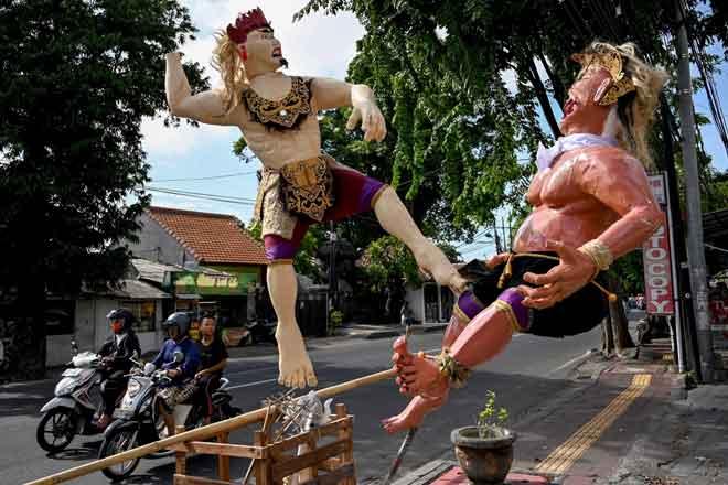 Penduduk menunggang motosikal melintasi patung dikenali sebagai Ogoh-Ogoh menjelang sambutan 'Hari Sepi' di Denpasar, Bali kelmarin. — Gambar AFP