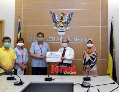 Zaidee menyerahkan cek berjumlah RM1 juta kepada Uggah.