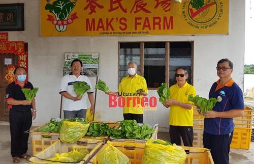 Ting (tengah), Mak (dua kiri) menunjukkan sayur yang akan diagihkan kepada penduduk Miri