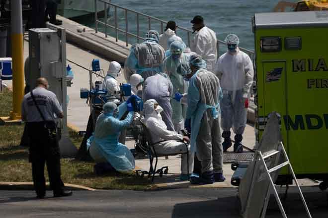 Pekerja perubatan membantu anggota kru kapal persiaran disyaki dijangkiti COVID-19 yang tiba di Pangkalan Pengawal Pantai Amerika Syarikat di Miami, Florida kelmarin. — Gambar AFP
