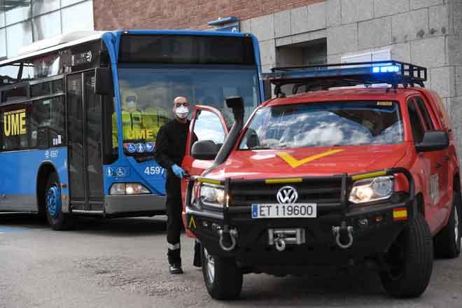 Anggota UME (Unit Kecemasan Tentera) bersiap sedia untuk memindahkan pesakit dari Klinik Hospital San Carlos dengan menaiki bas ke hospital sementara untuk pesakit COVID-19 di pusat pameran dan konvensyen Ifema di Madrid, kelmarin. — Gambar AFP