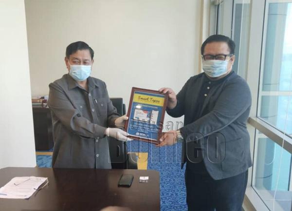 Aidi (kiri) menyempurnakan perasmian SmartTapau, sambil disaksikan Pengarah Urusan Smart Bah Technology Sdn Bhd, Mazrie Mahat.