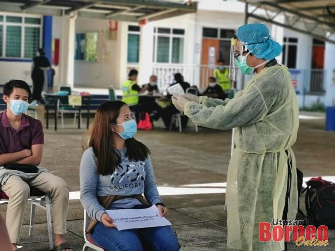 Pegawai kesihatan UNIMAS memeriksa suhu badan Laura Steven, antara pelajar yang dihantar pulang hari ini.