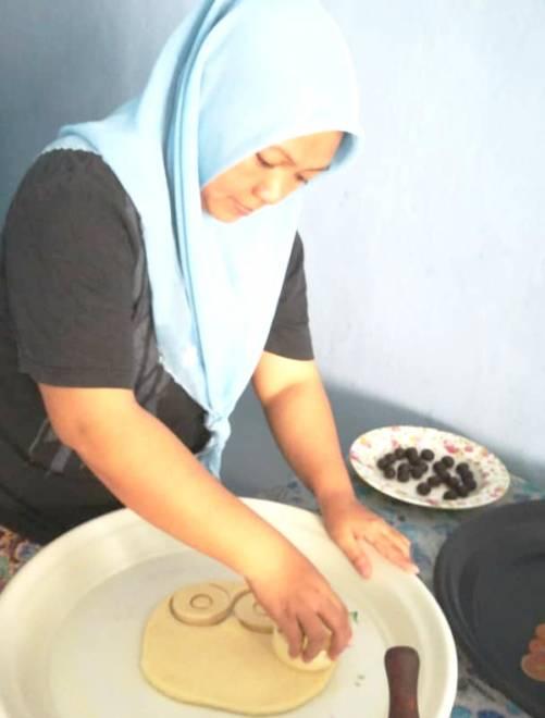 Faridah sedang membuat kuih untuk memenuhi permintaan pelanggan.