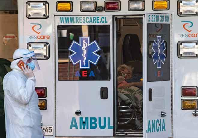 Wanita dengan simptom COVID-19 menunggu di dalam ambulans untuk dibawa ke hospital di Santiago, Chile kelmarin. Kira-kira separuh daripada 60 anggota senat Chile, termasuk empat menteri, diarahkan menjalani kuarantin selepas mempunyai kontak dengan sekurang-kurangnya tiga rakan setugas yang dijangkiti virus itu,  kata sumber rasmi kelmarin. — Gambar AFP